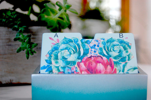 Mint green Rolodex Dividers with a green, blue, and pink succulent print in a pretty holder with plants in the background