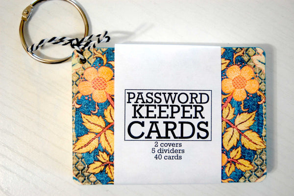 A blue tapestry password keeper - a suitable gift for a seamstress. The password keeper is wrapped  and has a silver ring. The print is a William Morris print with orange and yellow flowers and leaves.