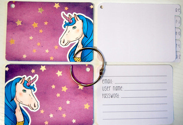Flat lay display of all of the elements of the unicorn password keeper: Front and back cover, silver ring, 5 purple dividers, and 40 purple password cards