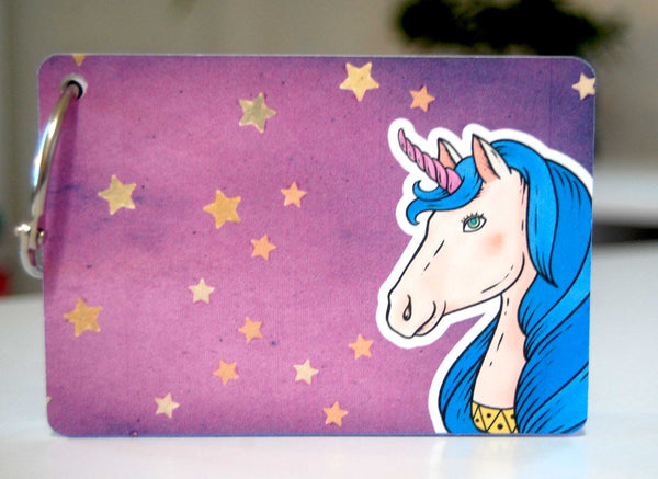 A colorful password keeper on a ring with a unicorn on the cover. the cover is a pretty purple with sparkling gold stars. The unicorn is shown from the neck up in the lower right corner. The hair is blue and the horn is pink.