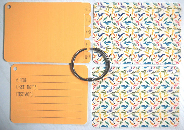 Flat lay display of all of the elements of the Watercolor Garden password keeper: Front and back cover, silver ring, 5 orange dividers, and 40 orange password cards