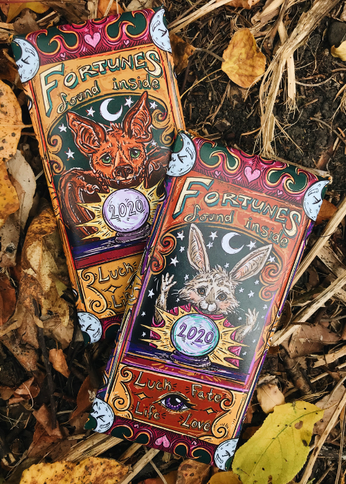 Image of 2020 Halloween Trick or Treat Limited Edition chocolate bar collaboration with Linda Ritter formerly of Salgado Fenwick. Wrapper features halloween design inspired by zoltar fortune teller with illustrated bat and bunny. Product features fortune card and milk chocolate with pop rocks, jujube candies and sprinkles.