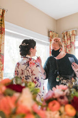 Image of Janna founder and makeup artist from Behind the Blush preparing a bride for her 2020 wedding at a home in Edmonton, Alberta, Canada. Image also features florals from FaBLOOMosity. Photo Credit: Sarah Mavro Photography