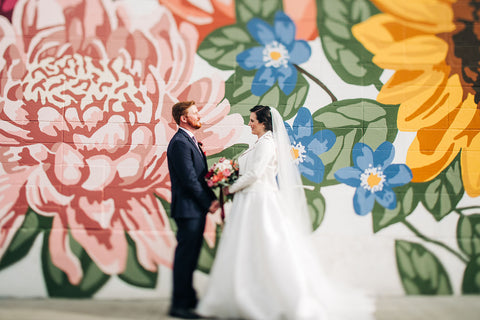 Image of wedding couple from 2020 featuring outfits by Derks Formal and Novelle Bridal standing in front of the mural at Manchester Square painted by artist Alixandra Jade based in Edmonton, Alberta, Canada. Photo credit: Sarah Mavro Photography