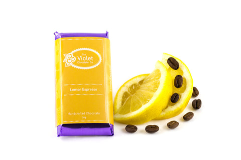 The Violet Chocolate Co. white chocolate flavoured with Calgary Heritage Roasting Co. Sumatra beans and lemon. Packaged bar sits next to slices of lemon and espresso beans.