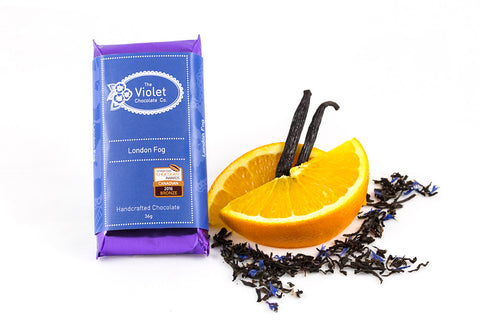 The Violet Chocolate Co. International Chocolate Awards Canadian 2016 Bronze Award winning packaged bar next to orange slices, loose-leaf Earl Grey tea and vanilla pods