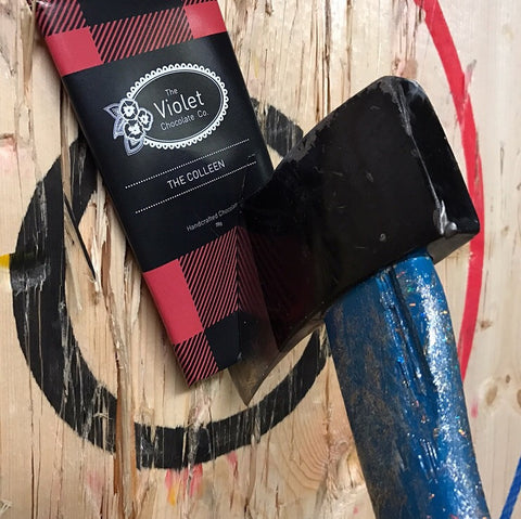 The Violet Chocolate Co. packaged The Colleen - milk chocolate Hazelnut Crunch wrapped in buffalo plaid against an axe throwing bullseye held in place by an axe