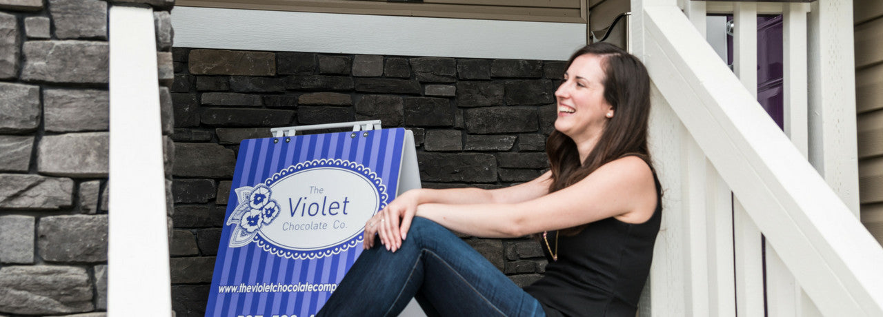 Rebecca sits in front of studio with sign of The Violet Chocolate Company click to learn more about her story