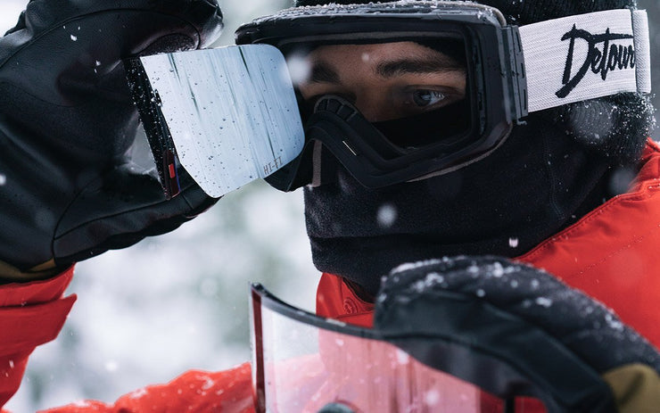 A man wears Detour silver snow goggles for skiing and snowboarding.