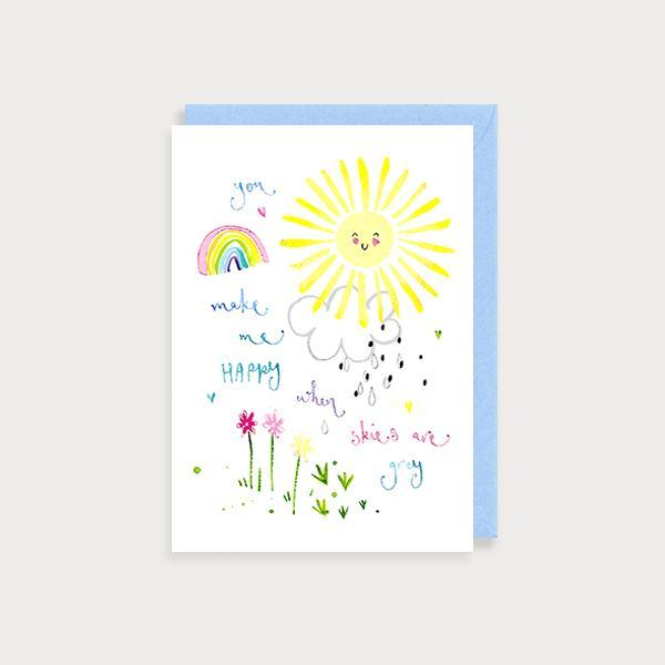 Image of illustrated just to say card with a big smiley sun, rainbow and flowers and the caption You Make me Happy When Skies are Grey
