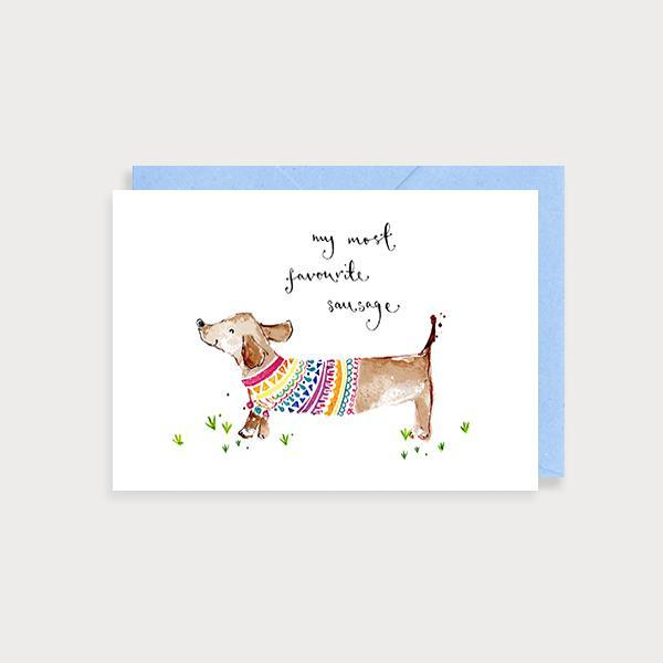 Image of illustrated anniversary or valentine's day card with a suasage dog in a jumper and the caption My Most Favourite Sausage