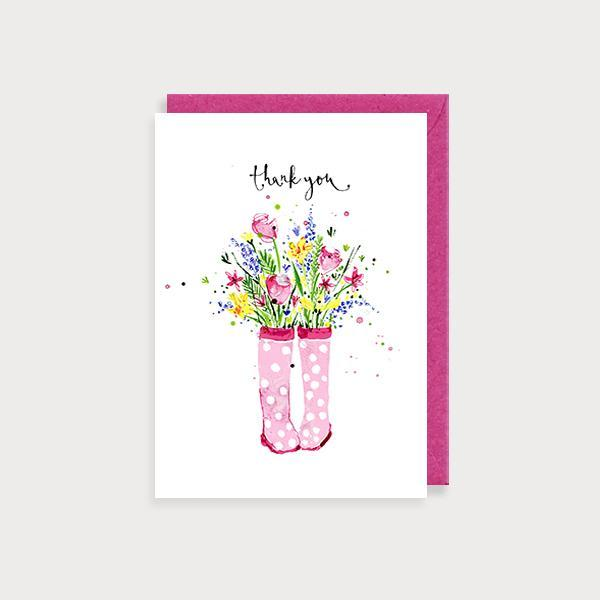 Image of ilustrated thank you card with a pair of pink polkadot wellies with a boquet flowers inside and the caption Thank You