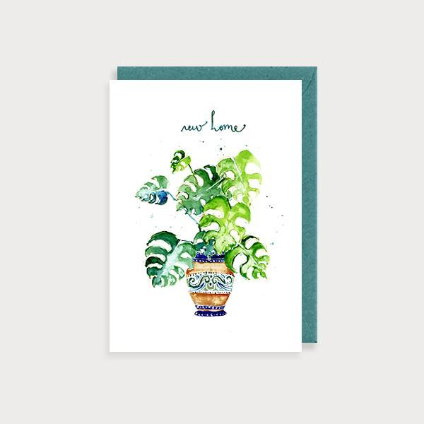 Image of ilustrated new home card with a cheese plant in a pot and the caption New Home