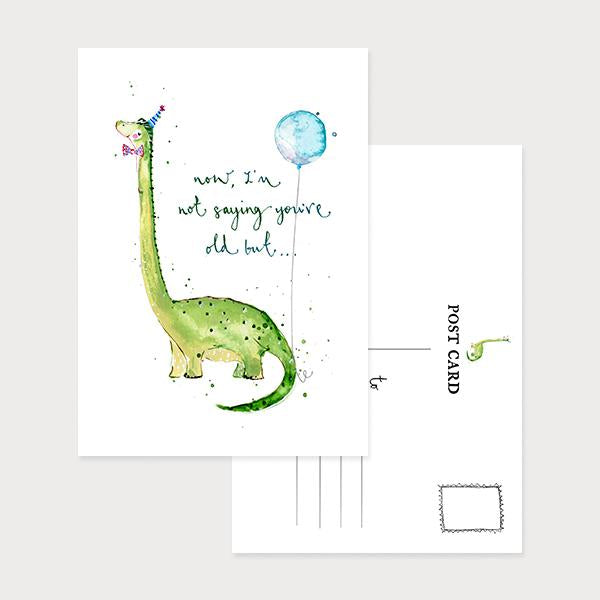 Image of an illustrated portrait postcard with a dinosaur in a bow tie and party hat and with a ballon and the caption Now, I'm Not saying You're Old But…