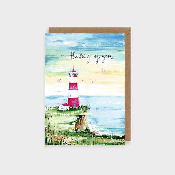 Image of illustrated thinking of you card of a lighthouse on hill and sea scene and the caption Thinking of You