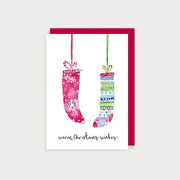 Image of illustrated christmas card with 2 hanging Christmas stockings and the caption Warm Christmas Wishes