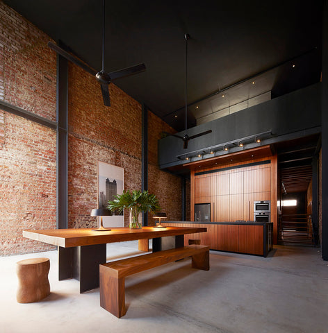 Large kitchen with exposed brick wall and timber and aluminium dining table.