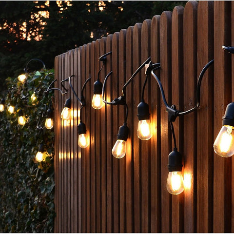 String of festoon lights with black cord and exposed bulbs hanging on outdoor fence