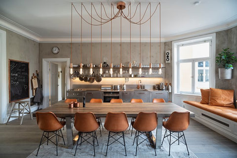 Kitchen with long table, brown chairs and gold pendant exposed light bulbs.