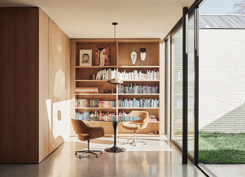 Stylish room with table, chairs, bookshelf and large window.