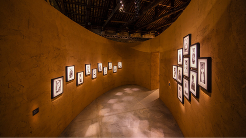 Hallway with many framed prints illuminated by light
