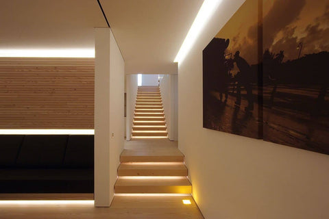 Staircase with warm lighting and large painting