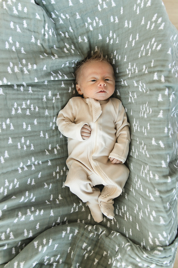 Baby sleeping on green pine swaddle blanket.