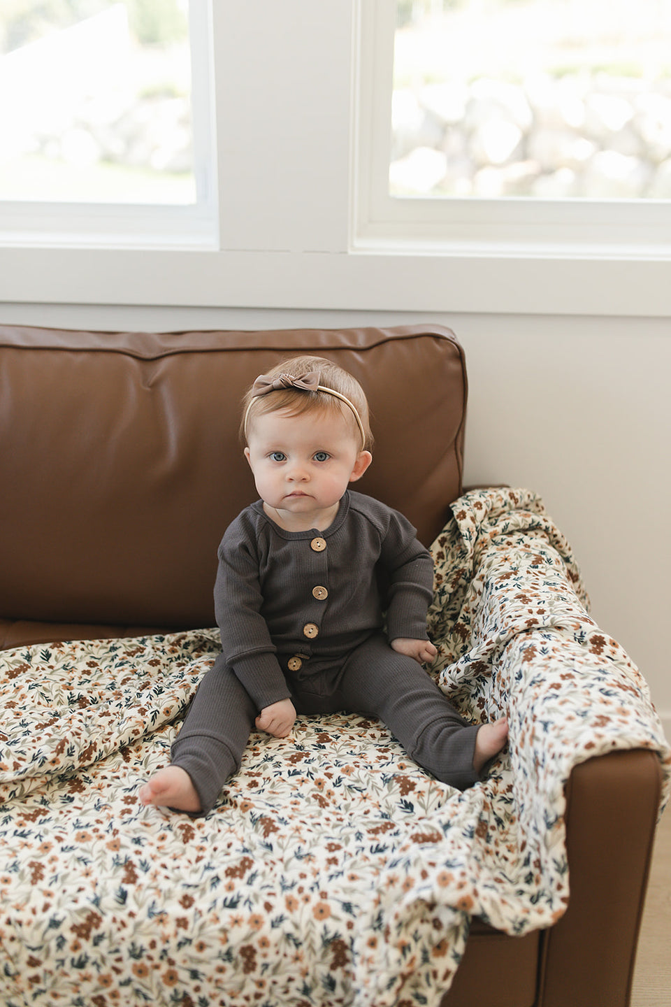 Baby Wearing Dusty Charcoal Romper Sitting on a Leather Sofa with Floral Swaddle
