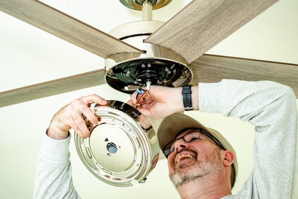 Hunter Fan Company employee installing a ceiling fan during Dorothy Day House of Memphis Huntervention