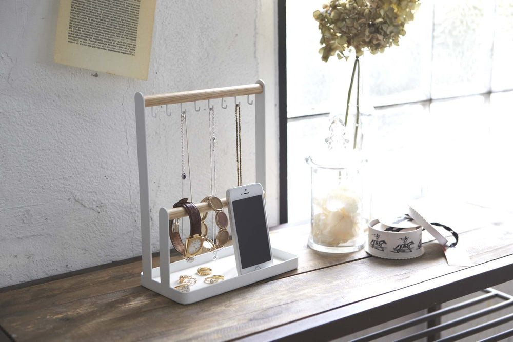 Wood and steel accessories tray filled with necklaces, watches, and mobile phone; sitting on a desk in a sunny room.