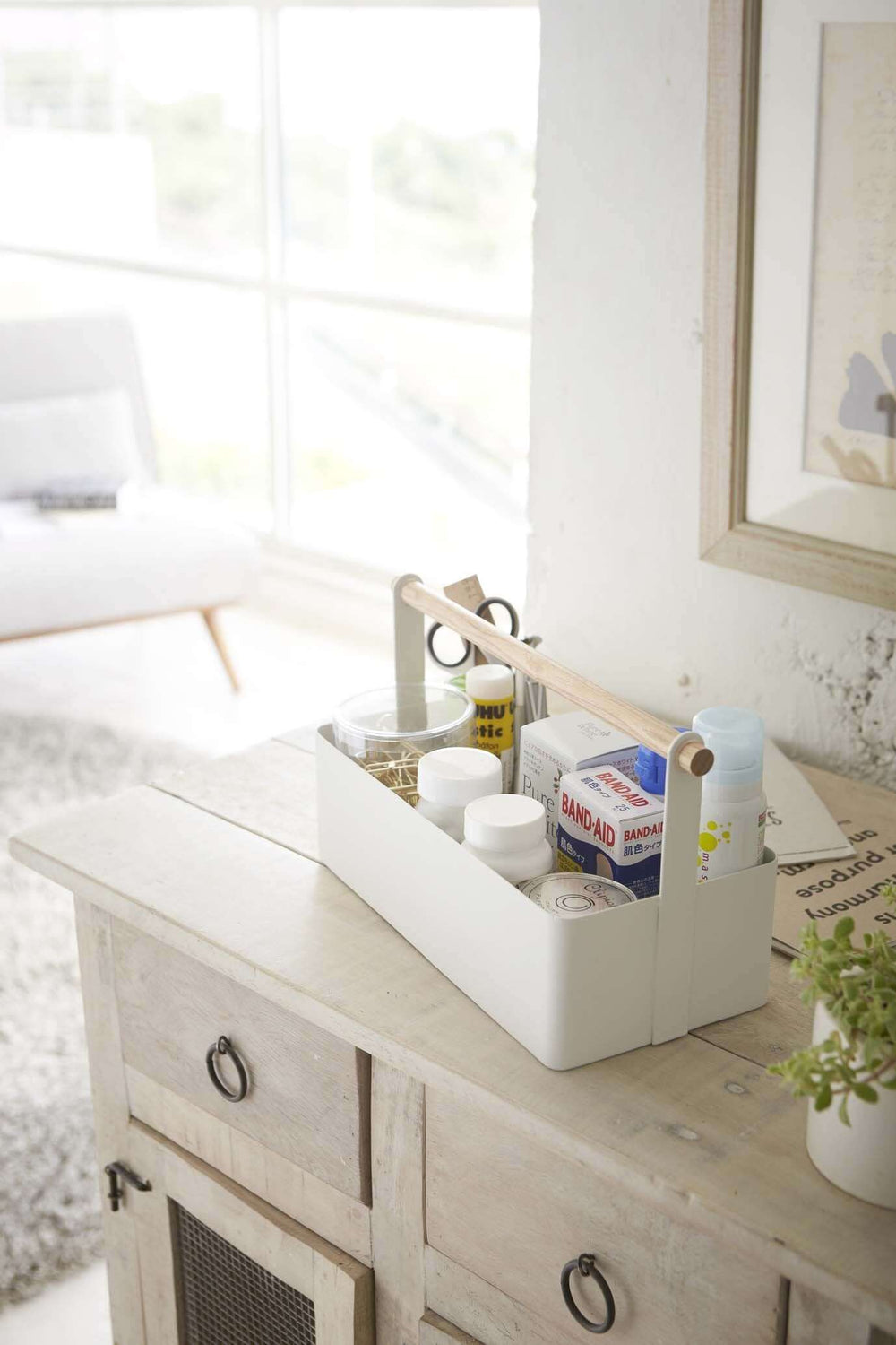 Rectangular white Yamazaki toolbox with wooden handle containing household items, sitting on dresser.
