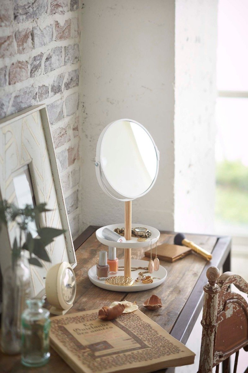 Yamazaki's Tabletop round mirror with tiered trays holding accessories on a dresser.