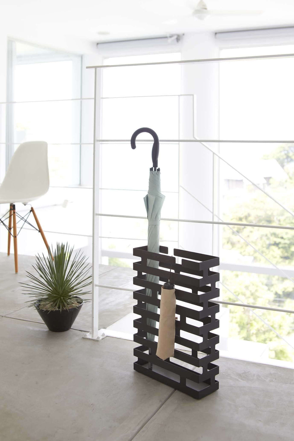 Wide Yamazaki umbrella stand black with brickwork-inspired design holding an umbrella and short umbrella at the entrance.