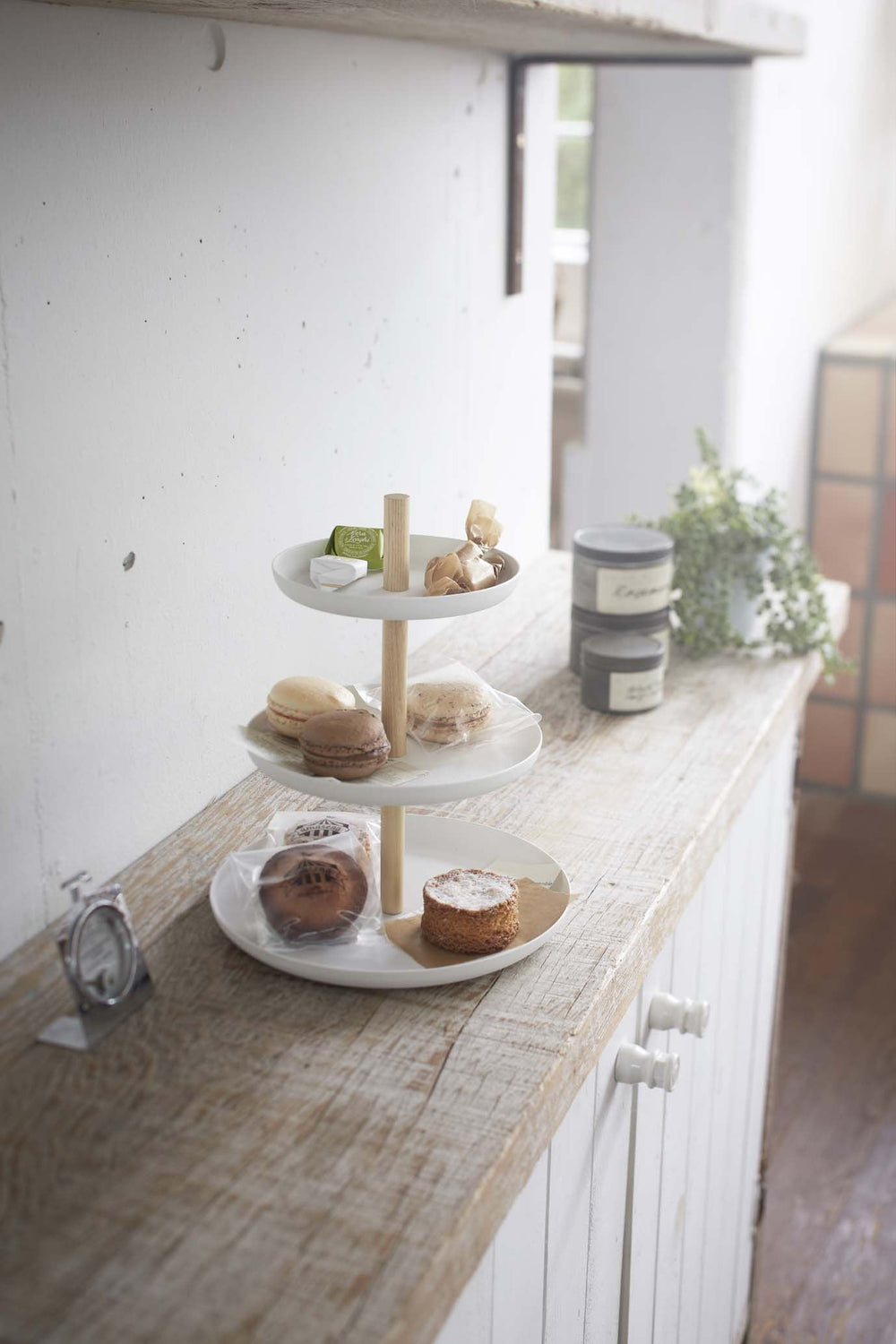 Three-tier Yamazaki tabletop server set with pastries on a kitchen shelf.