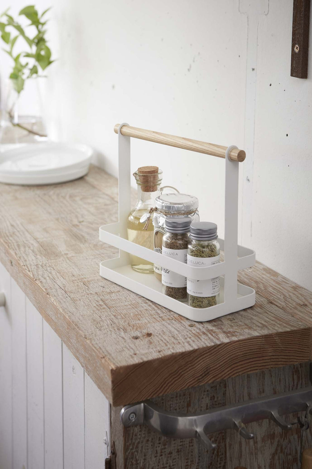 White metal spice rack holding spice canisters on a kitchen countertop