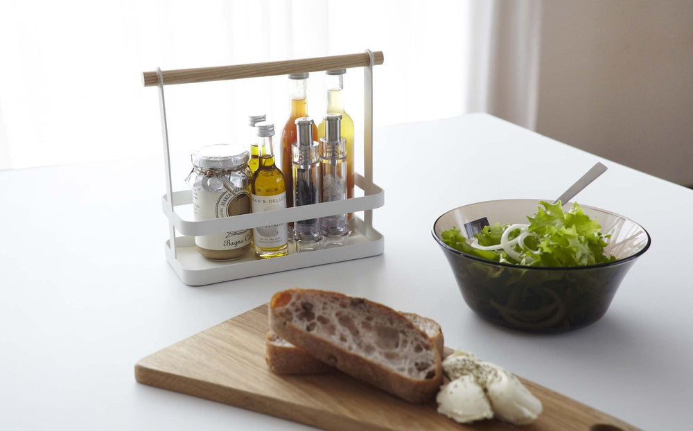 White metal spice rack holding spice canisters and oils on a kitchen countertop next to salad and bread.
