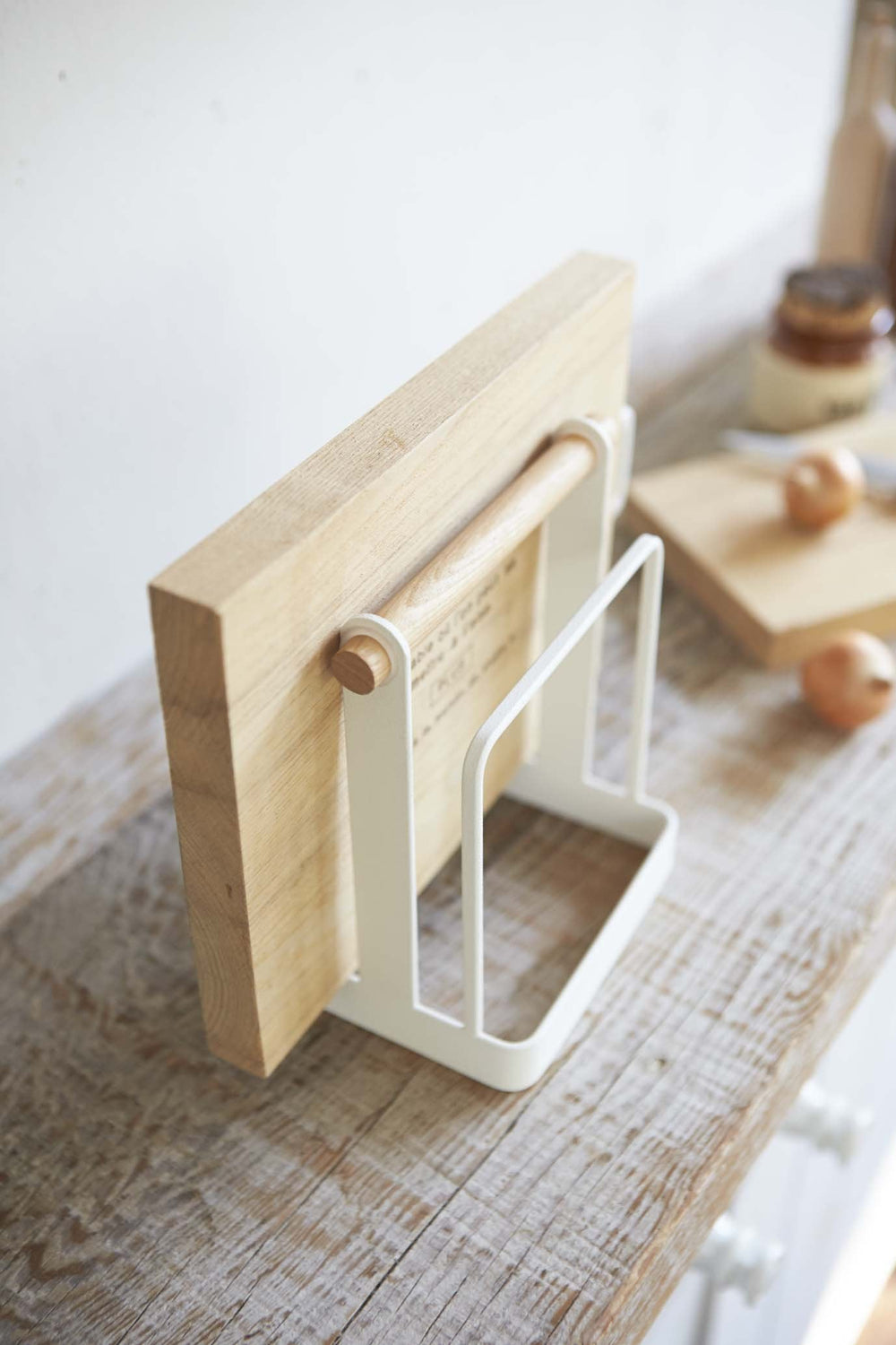 Angled view of Yamazaki Cutting Board Stand on countertop, holding a wooden cutting board