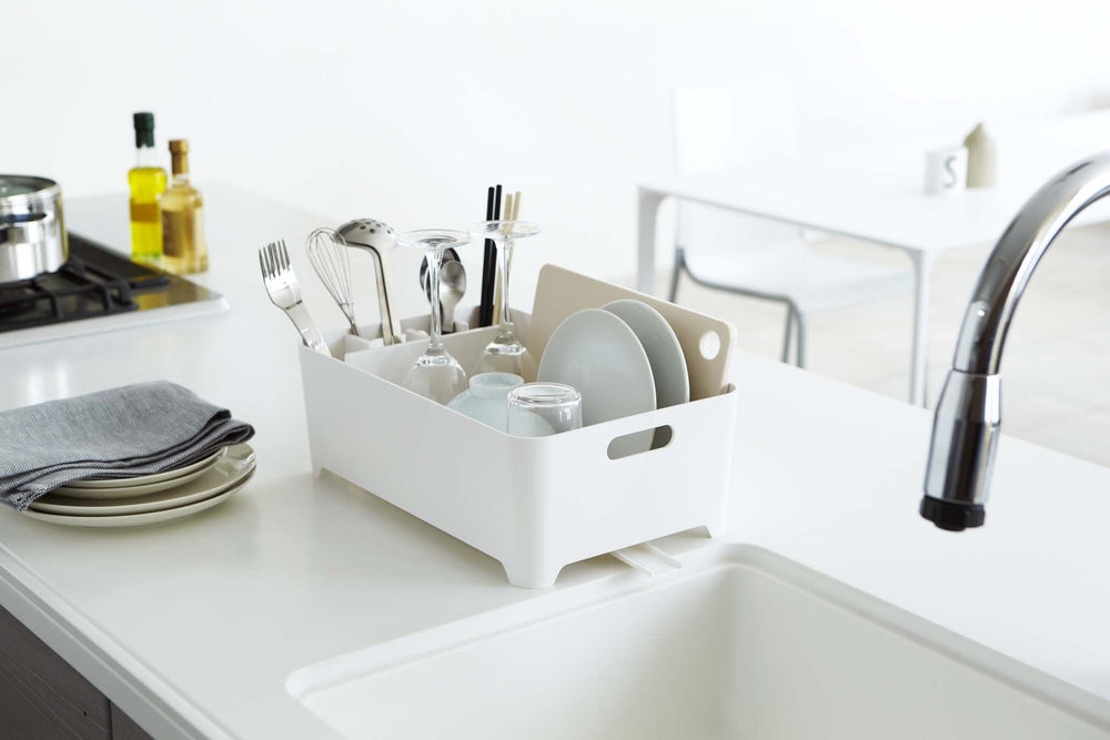 Yamazaki's white dish drainer with compartment filled with dishes sitting next to sink.
