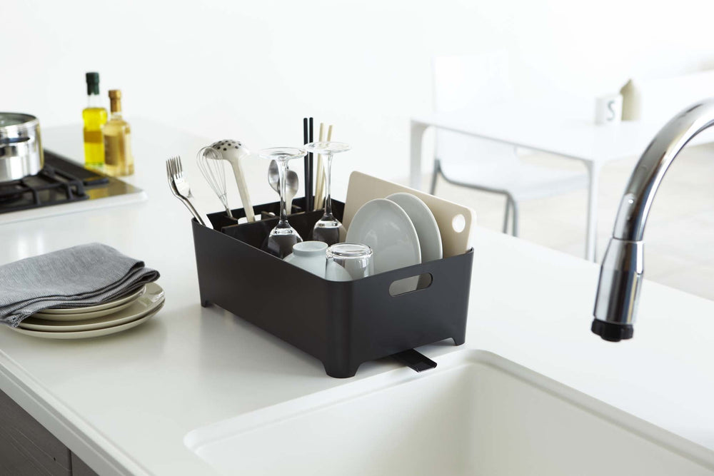 Yamazaki's black dish drainer with compartment filled with dishes sitting next to sink