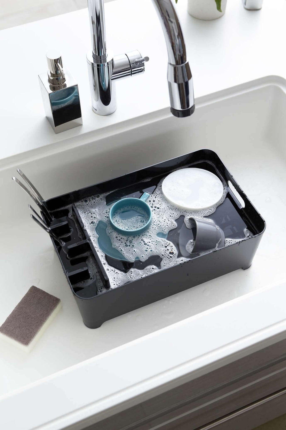 Yamazaki's black dish drainer with compartment filled with dishes and water in the sink