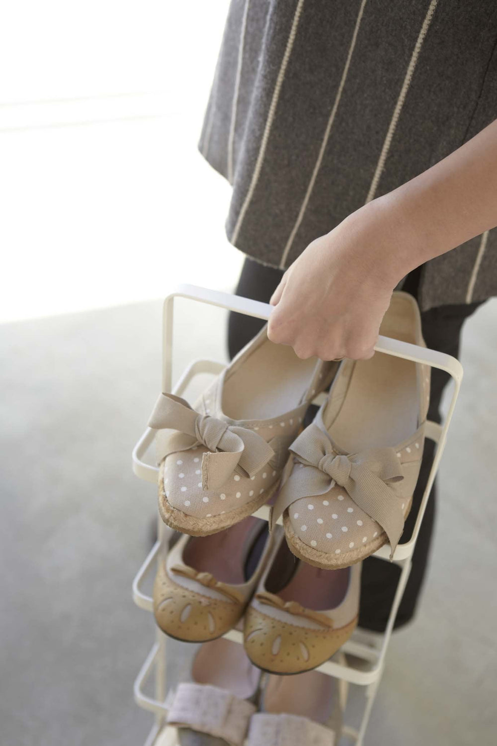 Someone carrying white Yamazaki shoe rack filled with shoes in a bedroom