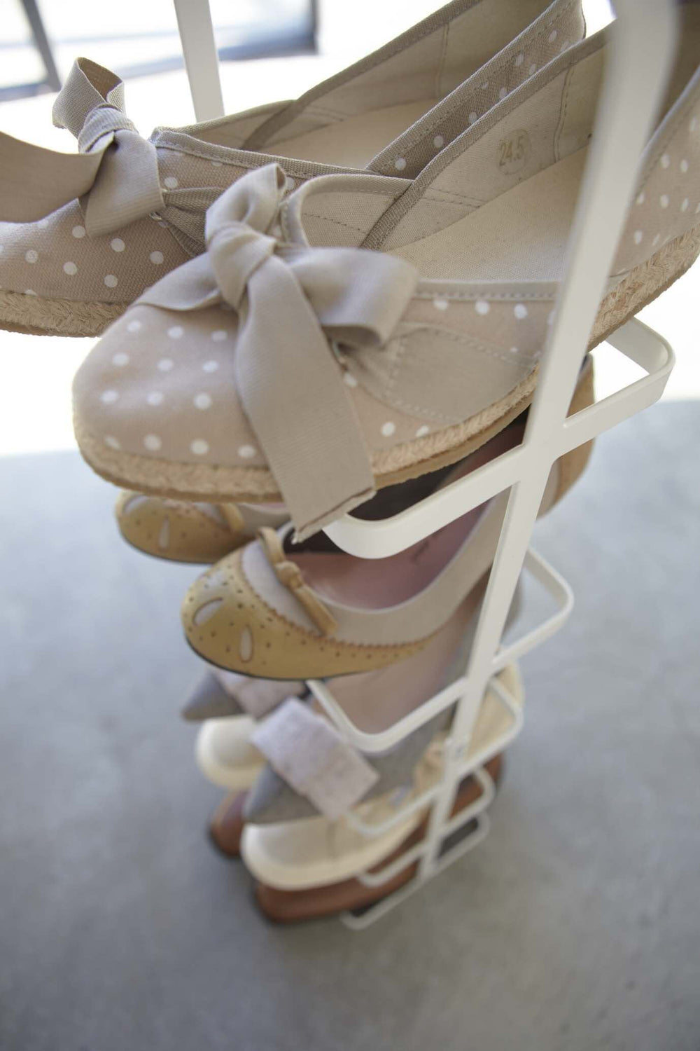 Close look at white Yamazaki shoe rack filled with shoes in a bedroom.