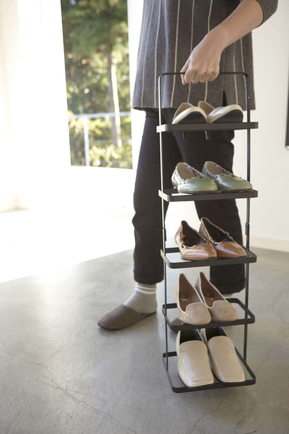 Someone carrying a black Yamazaki shoe rack filled with shoes in a bedroom