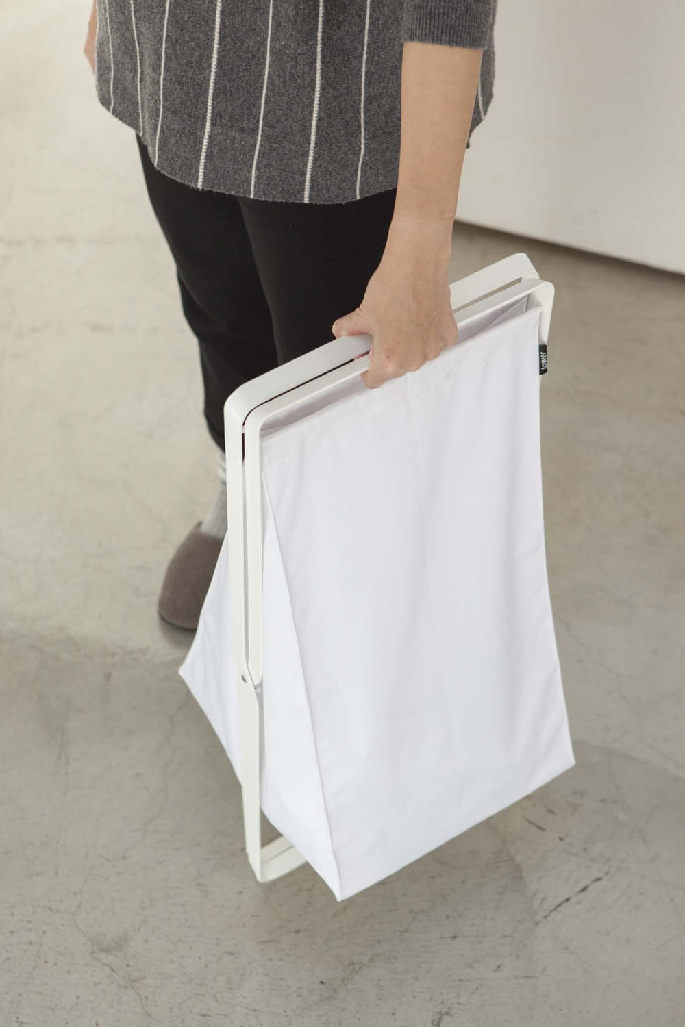 Someone is carrying Yamazaki's white folded-up laundry hamper.