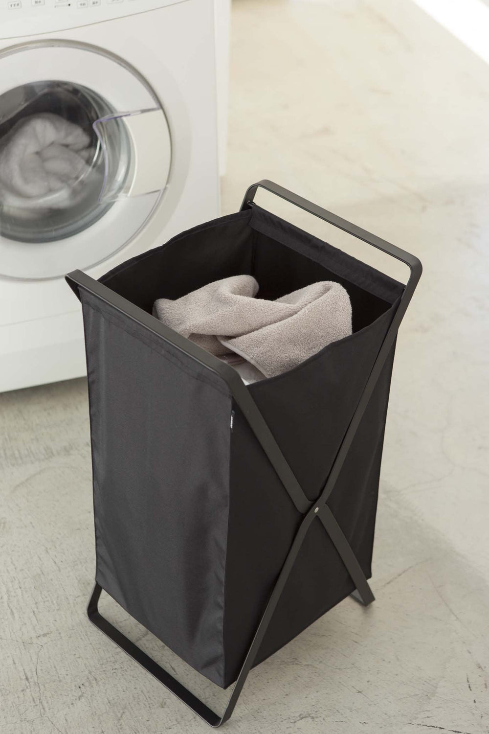 Yamazaki's black cloth collapsible laundry hamper next to a washing machine