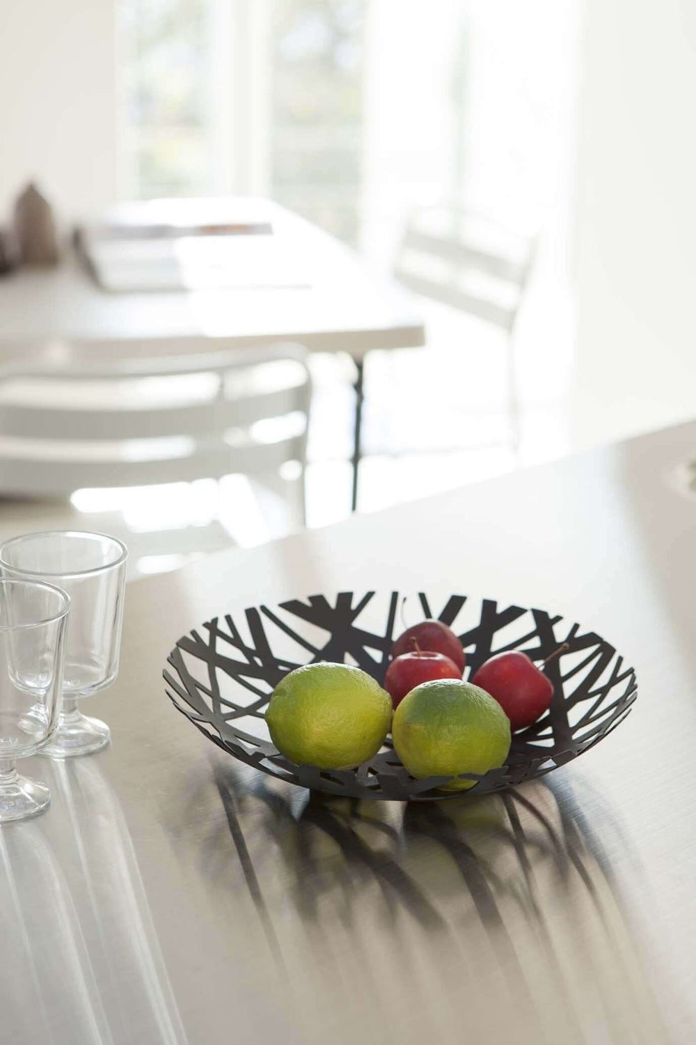 Black Yamazaki fruit bowl with cutouts holding fruit in a kitchen.