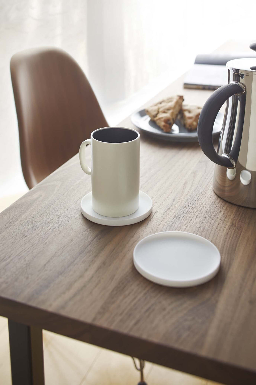 Two Yamazaki white round coasters on the wooden table. One of them hold a white mug