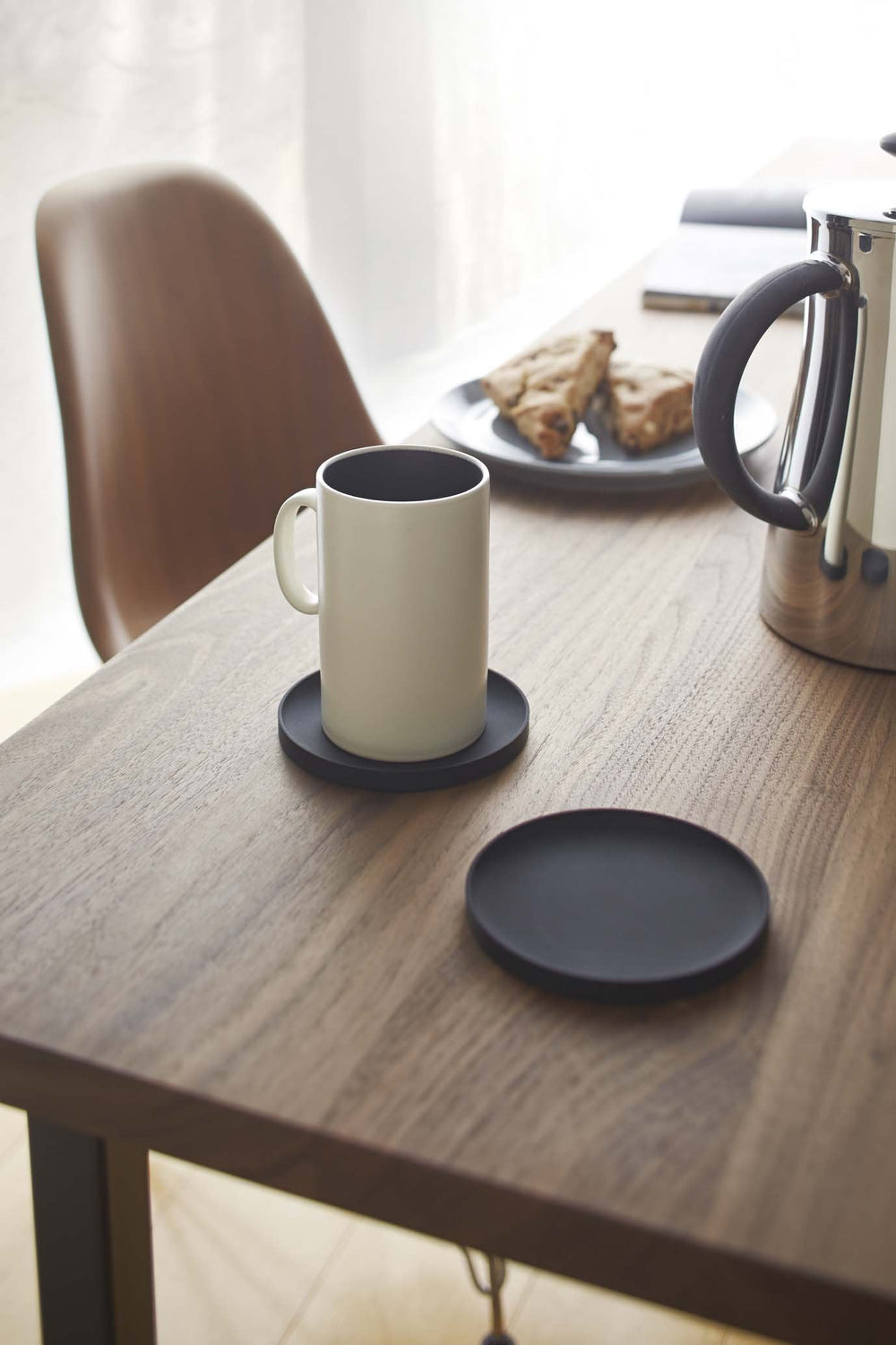 Two Yamazaki black round coasters on the wooden table. One of them hold a white mug