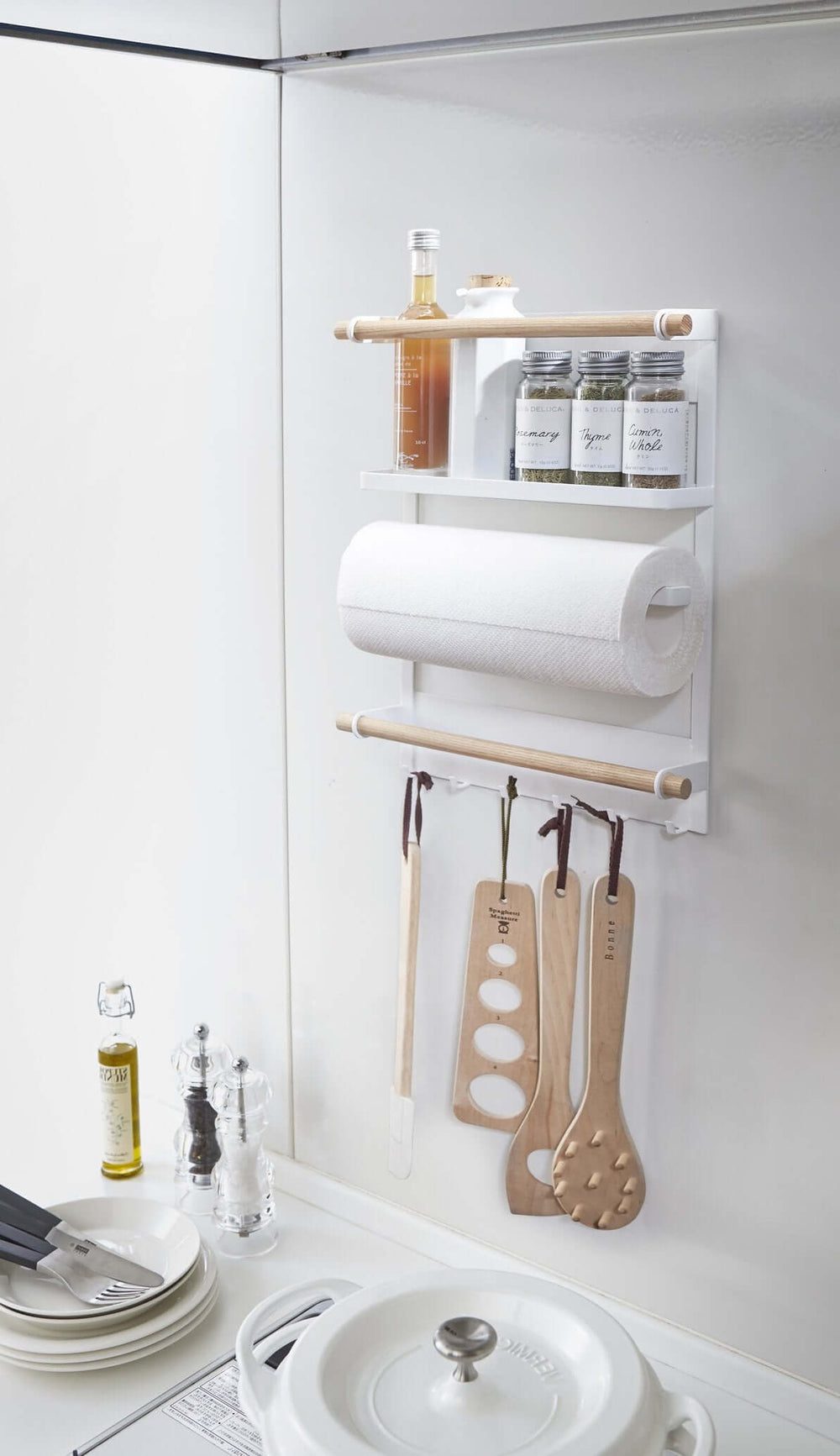 Yamazaki's white magnetic organizing rack holding kitchen and cooking supplies on the fridge