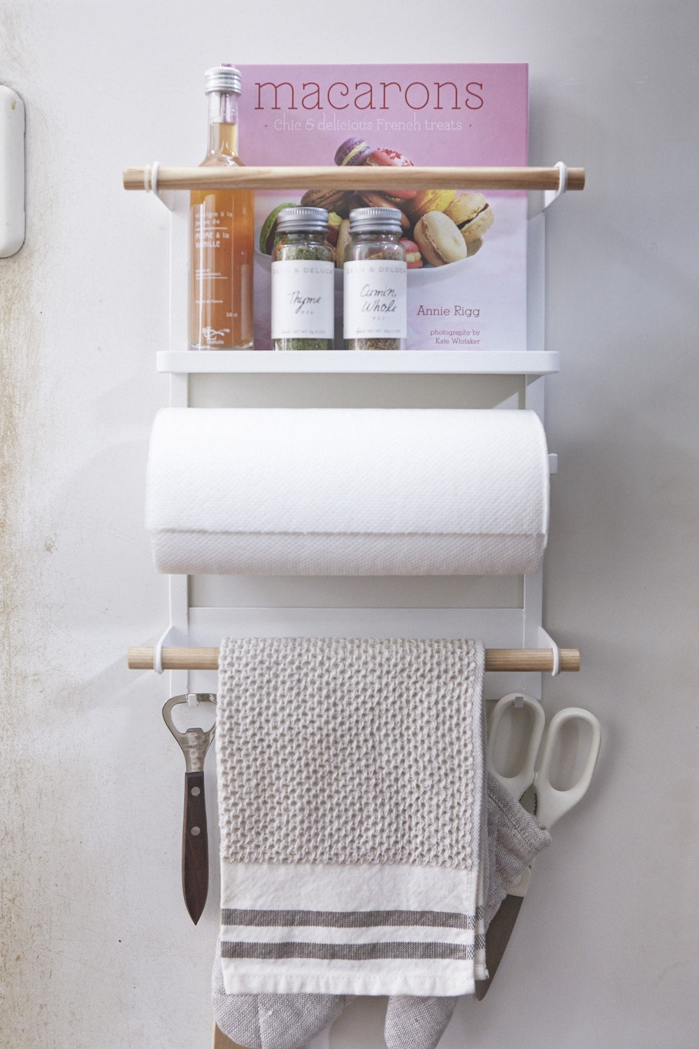 Yamazaki's white magnetic organizing rack holding kitchen and cooking supplies on the fridge.